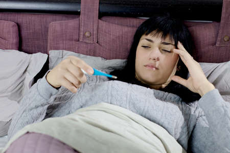 caucasian fever: Young woman in bed with fever