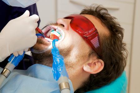 Sufrimiento del hombre durante el blanqueamiento de dientes