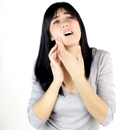 Unhappy woman isolated holding her jaw for pain