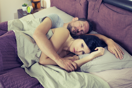 cheating woman: Unhappy sad woman in bed with sleeping boyfriend depressed Stock Photo