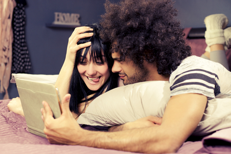 Man and woman having fun taking picture in bed photo