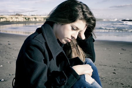 holding on head: Depressed young teenager holding head
