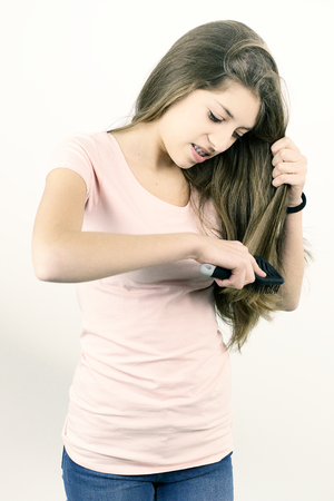 long silky hair: Cute girl isolated brushing long silky blond hair Stock Photo