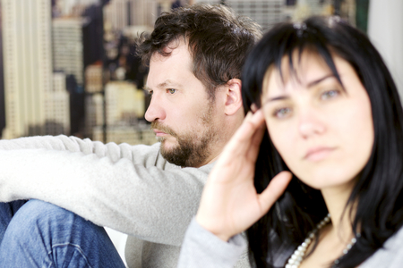 family fight: Sad man sitting on couch unhappy with girlfriend