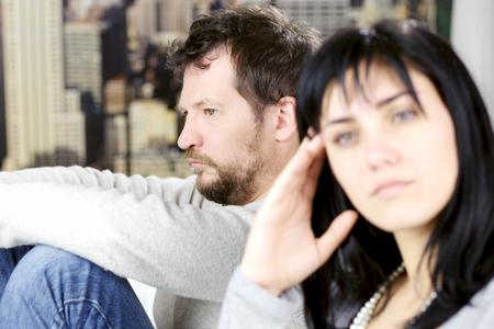 Trieste man zittend op de bank ongelukkig met vriendin