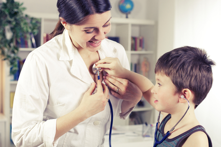stethoscope boy: Happy boy playing with doctor in hospital