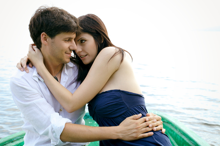 Happy couple in love on boat in vacation photo