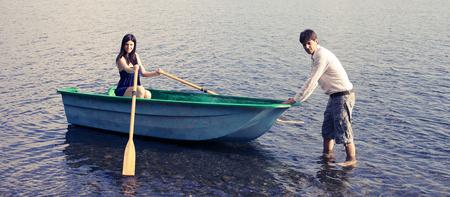 Happy couple having fun with wood boat photo