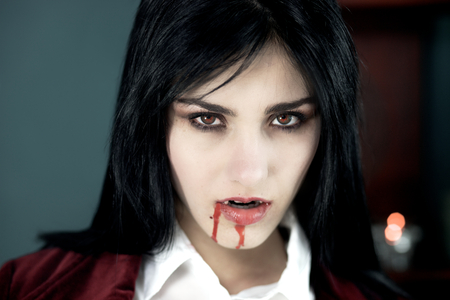 female eyes: Scary vampire pale looking with red eyes Stock Photo
