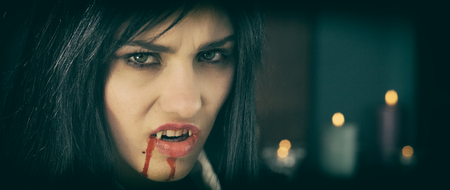 Gorgeous woman vampire angry with blood photo