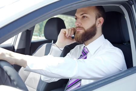 Ernstige jonge executive man met stropdas en wit overhemd in de auto op de telefoon