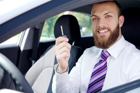 Feliz el hombre de negocios sonriente con el nuevo coche