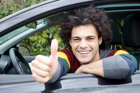 Hombre italiano joven fresco que se sienta en el nuevo coche feliz