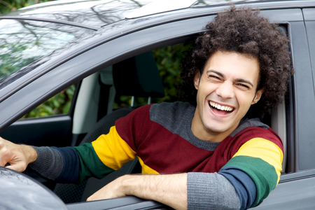 Young good looking modern man sitting in car laughing photo