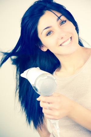 Muchacha sonriente feliz con secador de pelo