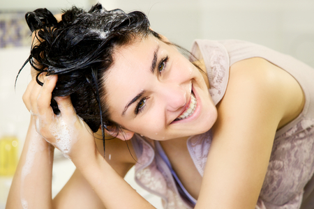white wash: Cute girl in bathroom washing hair with shampoo Stock Photo