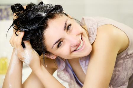 Linda chica en lavar el cabello con champú baño