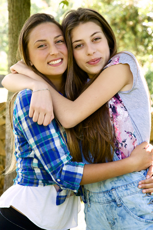 Two cute blonde female teenager showing affection photo