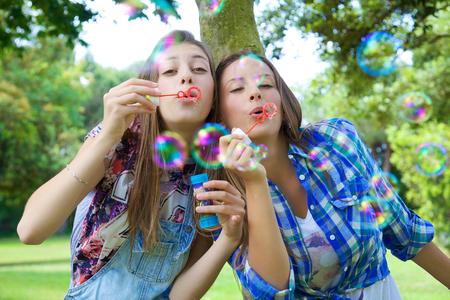 chicas adolescentes: Adolescente lindo jugando con pompas de jabón en el verano Foto de archivo