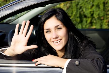 personas en la calle: Mujer joven linda que se sienta en el interior del coche saludando con la mano