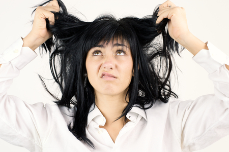 young attractive woman with black hair unhappy and strsssed about her hair. Funny expression