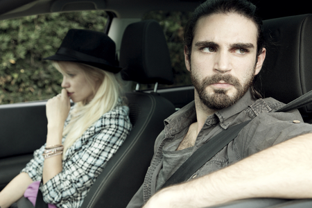 angry man mad at woman after fighting, sitting in car