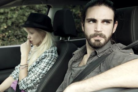 pareja enojada: loco hombre enojado con la mujer después de la lucha, sentado en el coche Foto de archivo