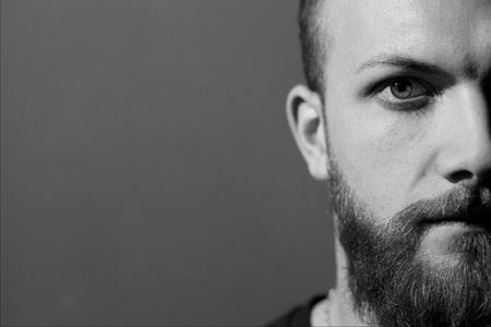 녹색 눈과 수염을 찾고 카메라로 멋진 남자의 절반 얼굴