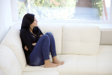 jolie seule femme brune regardant dehors perdue dans ses pensées
