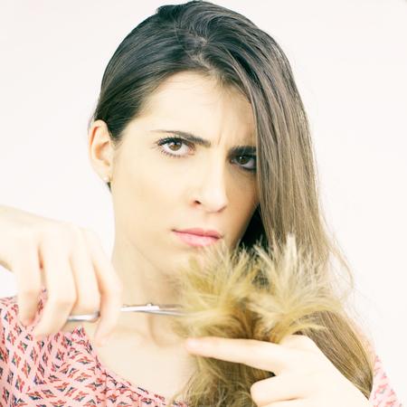 split ends: Woman making funny face looking split ends hair