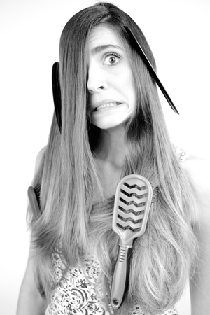 too many: Young woman unhappy about too many hair with brushes and comb in it Stock Photo