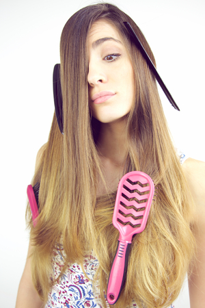bad hair day: Young woman unhappy about too many hair with brushes and comb in it Stock Photo