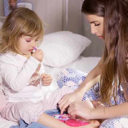 niñas pequeñas: Bebé feliz lindo con la madre jugando con el maquillaje para los niños