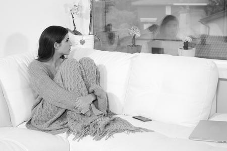Beautiful young sad depressed woman sitting on sofa Stockfoto