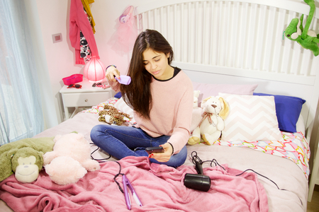 young and happy latina girl who dries her long black hair sitting on the bed