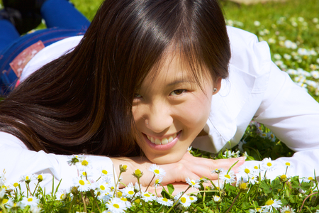 Cute Chinese lady smiling happy in front of flowers