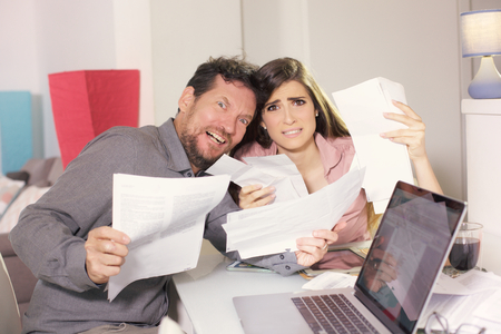 young couple at home looking bills calculating with pc and tablet