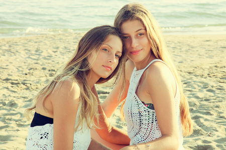 Happy girls with long hair feeling air sitting on sand Stockfoto