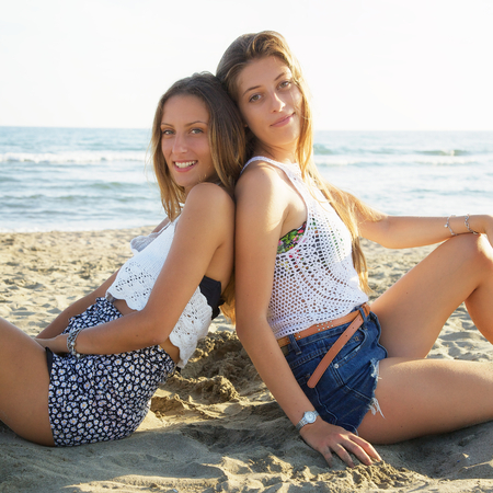 Happy girls with long hair feeling air sitting on sand Standard-Bild