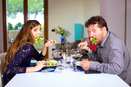 man and woman eating salad making funny expression