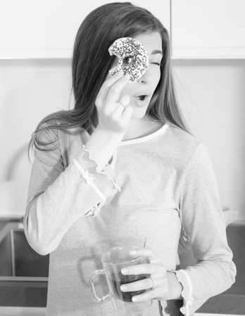 Happy young woman in the morning holding donut having fun