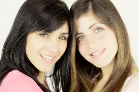 Two beautiful young women showing strong friendship looking camera Stockfoto