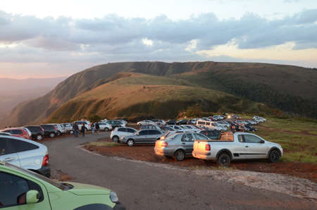 Cars lined up at sunset on a curve in Topo do Mundo (translated to Top of the World) in Minas Gerais