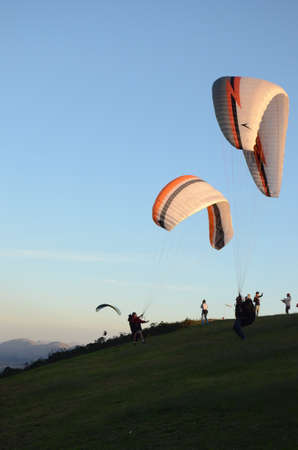 Two Paraglidings rising at sun set in Topo do Mundo (translated to Top of the World) in Minas Gerais Editorial