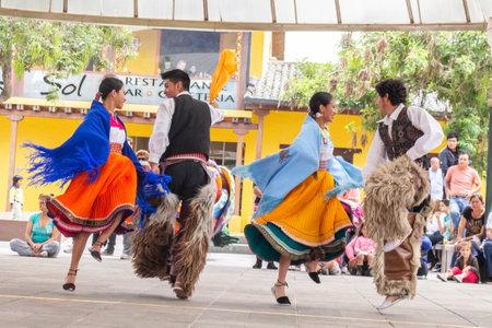 Donne e uomini in costumi tipici degli indiani sudamericani che ballano con costumi tradizionali colorati Editoriali