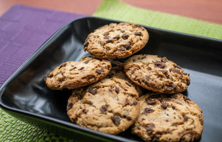Close-up of chocolate chip cookies on colored tablecloths inside a black plate Banco de Imagens