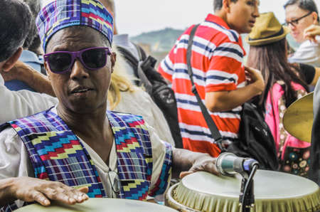 Close-up of musician percussionist with dark glasses, tourists are seen in the back