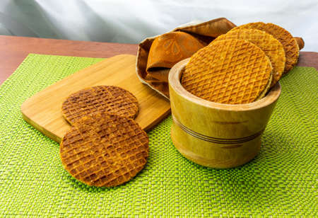 Shot of three quarters of a group of stroopwafels on a kitchen board inside a bowl Stockfoto