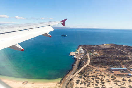 Shot taken from the window of an airplane where the wing is seen and below an island and a ship sailing