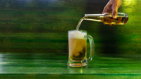 Mug of beer that is being served from a bottle on a green wooden table on a gray concrete background